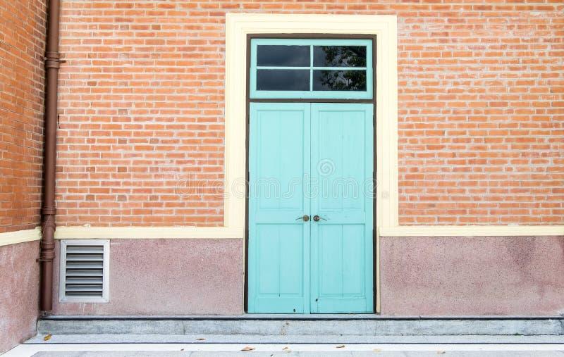 在橙色砖墙,外部大厦的蓝色门 库存照片