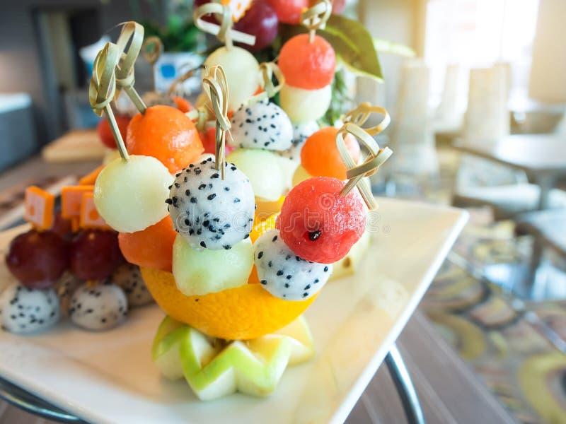 在橙色碗的可口新鲜水果沙拉球 免版税库存照片
