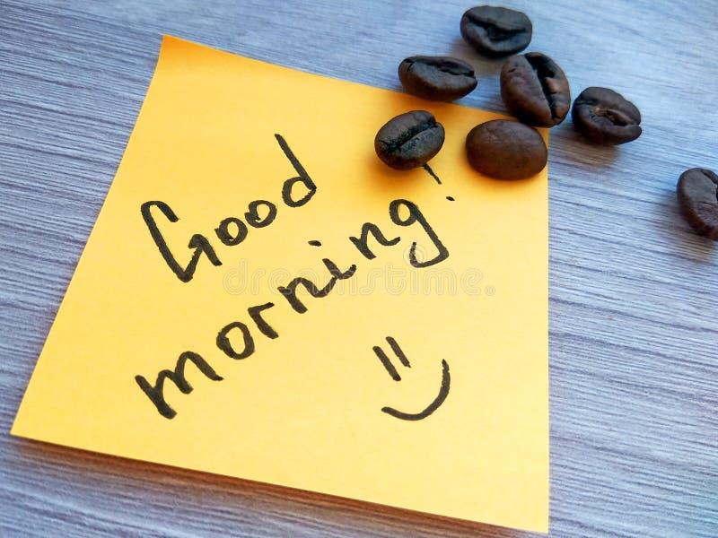 在橙色稠粘的笔记的早晨好手写的消息与在木背景的咖啡豆 图库摄影