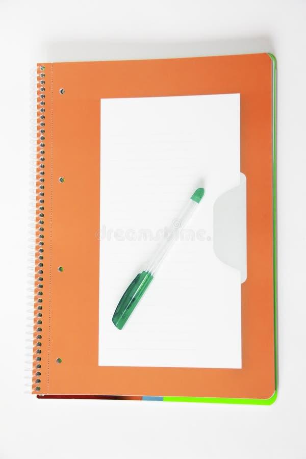 在橙色笔记本背景的绿色学生胶凝体笔  图库摄影