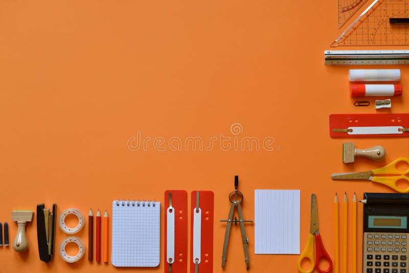 在橙色纸板的办公室或学校用品 免版税库存图片