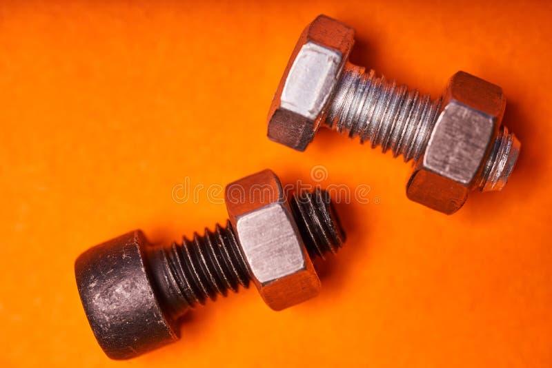 在橙色背景特写镜头的Bolted连接的元素 库存照片