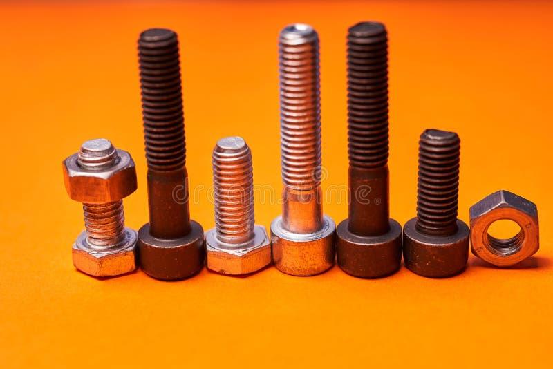 在橙色背景特写镜头的Bolted连接的元素 免版税库存照片