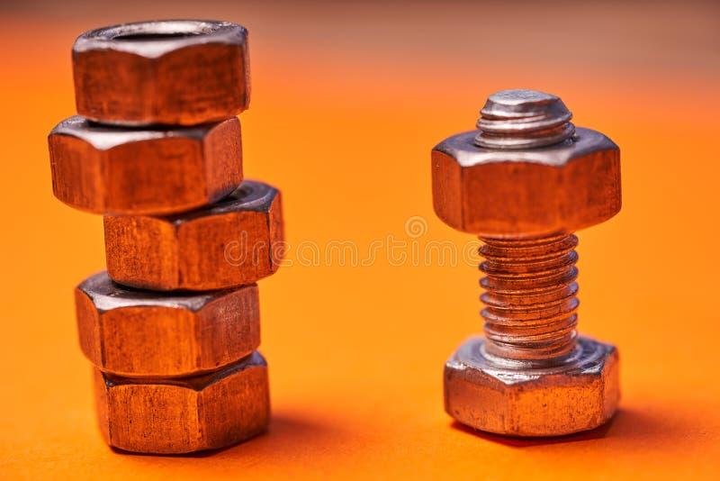 在橙色背景特写镜头的Bolted连接的元素 库存图片
