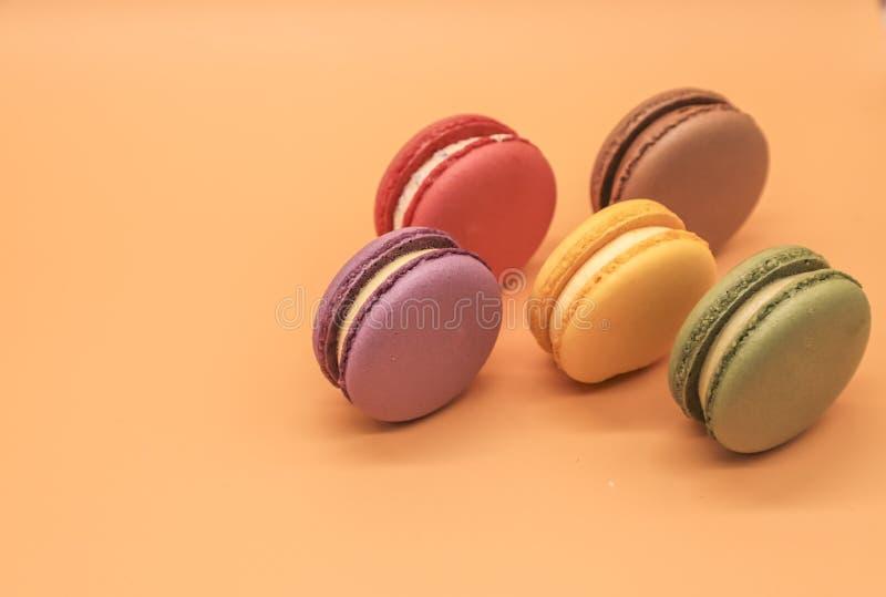 在橙色背景的五颜六色的蛋白杏仁饼干蛋糕 库存图片