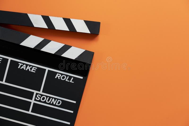 在橙色背景的电影拍板;影片、戏院和vedio摄影概念 图库摄影