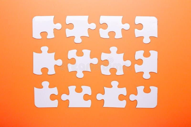 在橙色背景的白色难题 顶视图 库存图片
