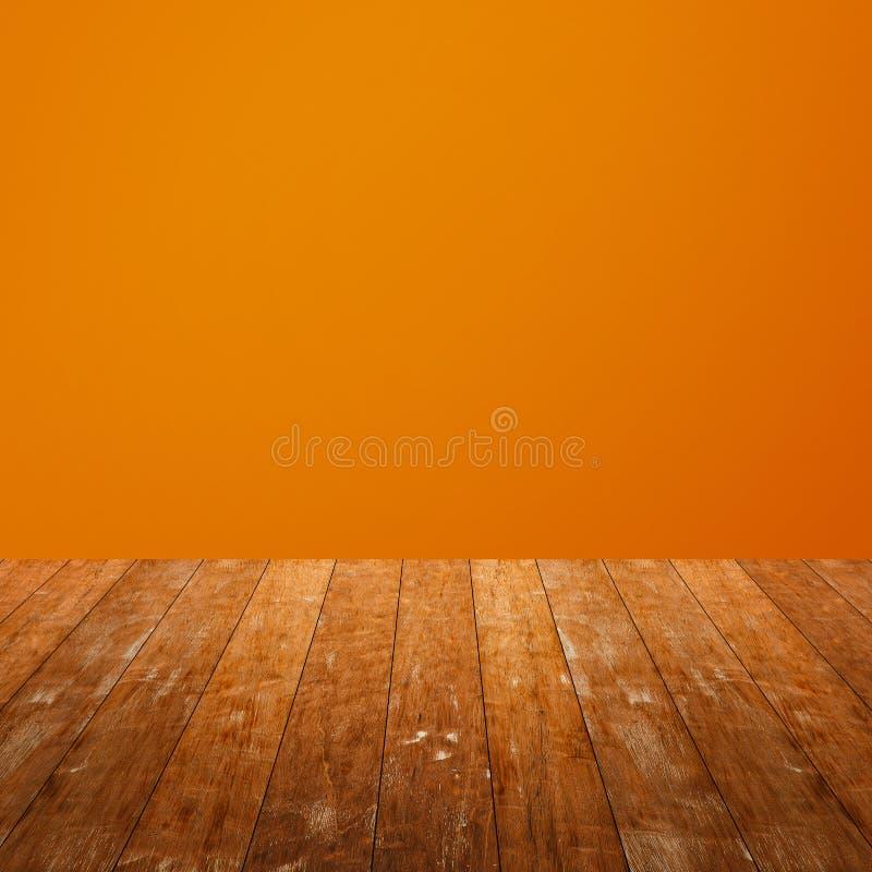 在橙色背景隔绝的木桌 免版税库存图片