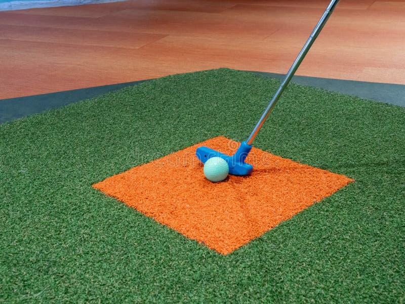 在橙色草皮的绿色高尔夫球旁边排队的草皮的蓝色轻击棒在小小高尔夫球路线 库存图片