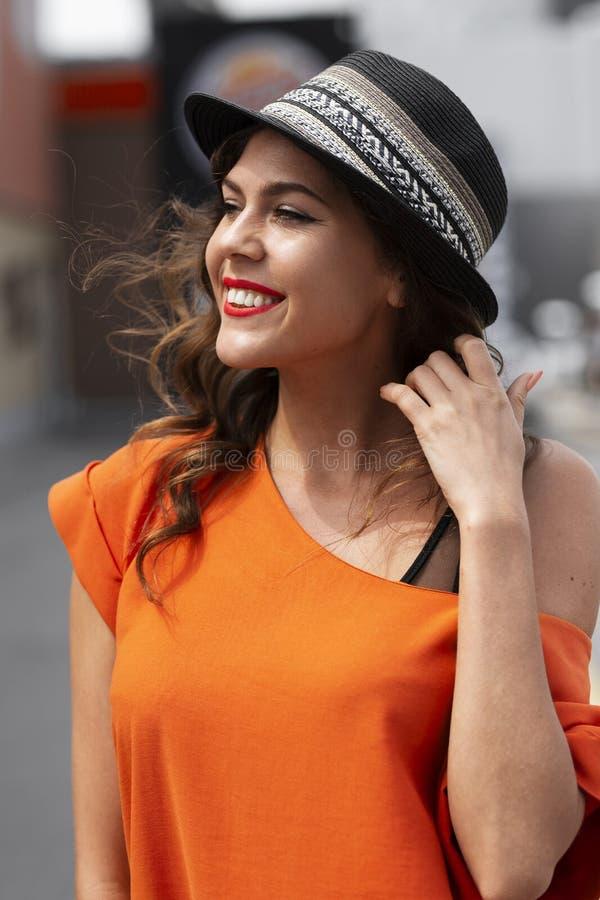 在橙色衬衣和帽子身分打扮的美丽的微笑的女孩室外在一个夏日 免版税库存图片