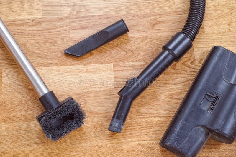在橡木地板上的肮脏的吸尘器刷子 图库摄影