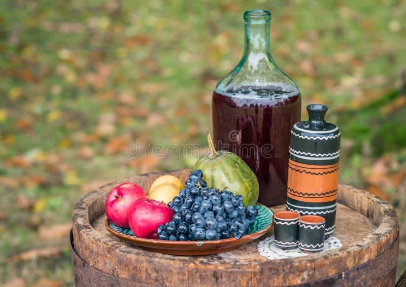 在橡木桶的静物画果子和红葡萄酒秋天 库存照片