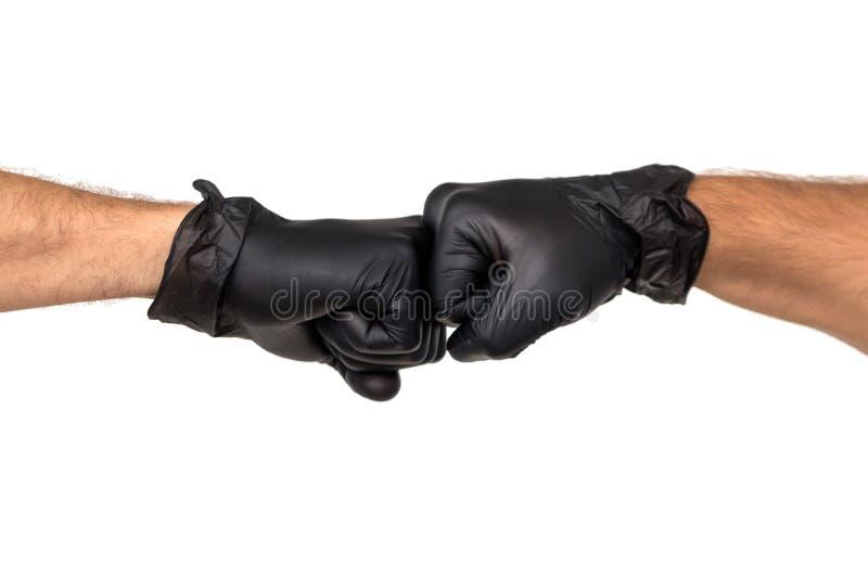 在橡胶手套的两只男性手被握紧入拳头 孤立 库存图片