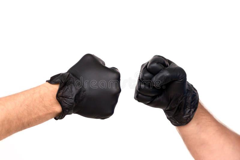 在橡胶手套的两只男性手被握紧入拳头 孤立 免版税库存图片