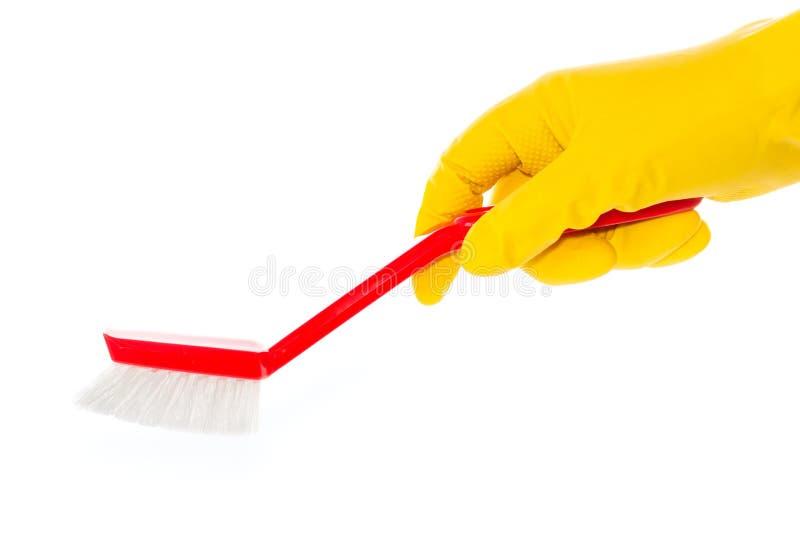 在橡胶手套的手与红色洗碗盘行为刷子 图库摄影