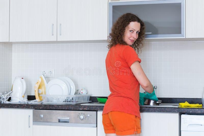 在橡胶手套的主妇洗涤的盘 库存图片