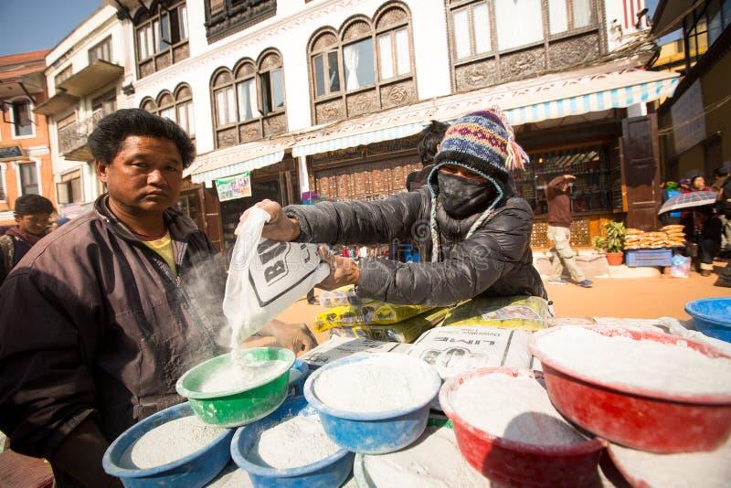 在欢乐庄严的Puja期间,在stupa Boudhanath附近供以人员捐赠的出售水泥的修理 图库摄影