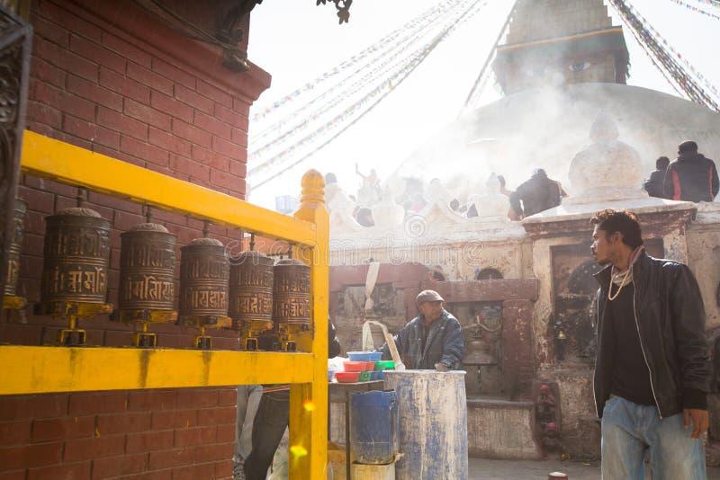 在欢乐庄严的Puja期间,在stupa Boudhanath附近供以人员捐赠的出售水泥的修理 免版税图库摄影