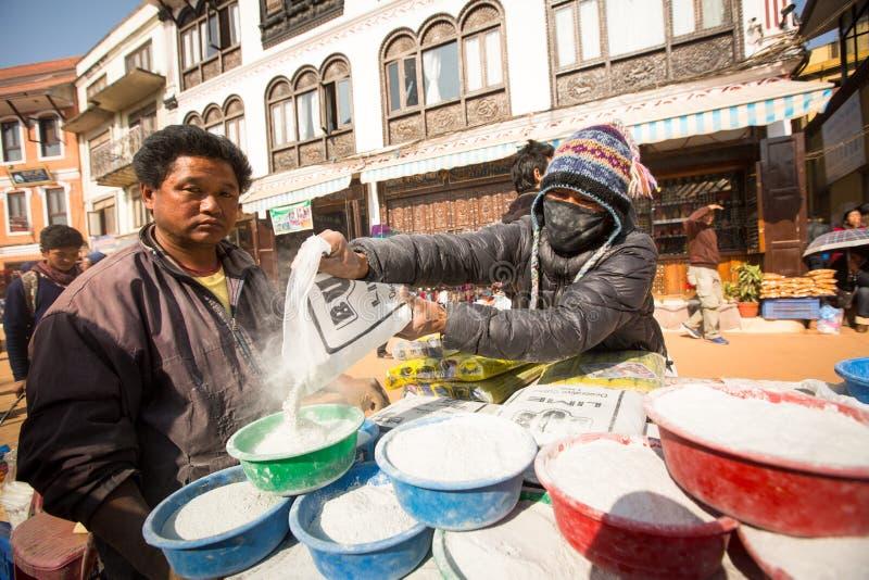 在欢乐庄严的Puja期间,在stupa Boudhanath附近供以人员捐赠的出售水泥的修理 免版税库存照片
