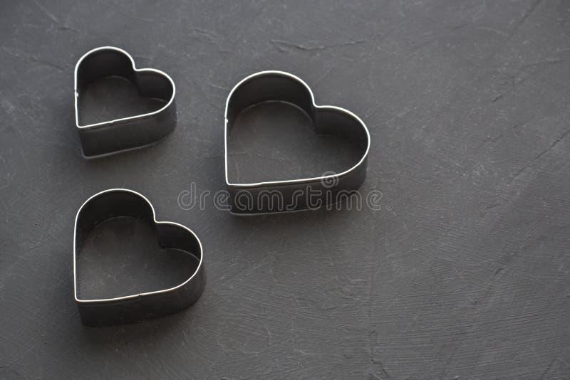 在欢乐黑背景的金属心脏 烘烤的模子 曲奇饼切削刀 平的位置,顶视图 图库摄影