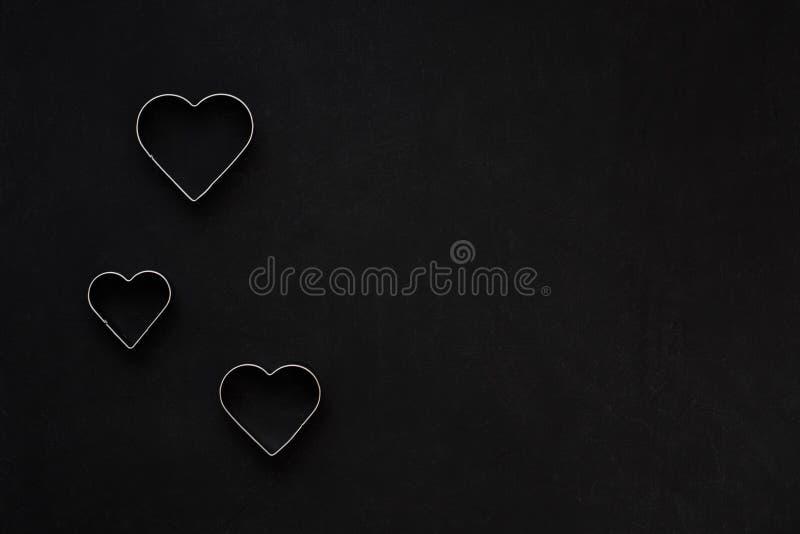 在欢乐黑背景的金属心脏 烘烤的模子 曲奇饼切削刀 平的位置,顶视图 免版税库存照片