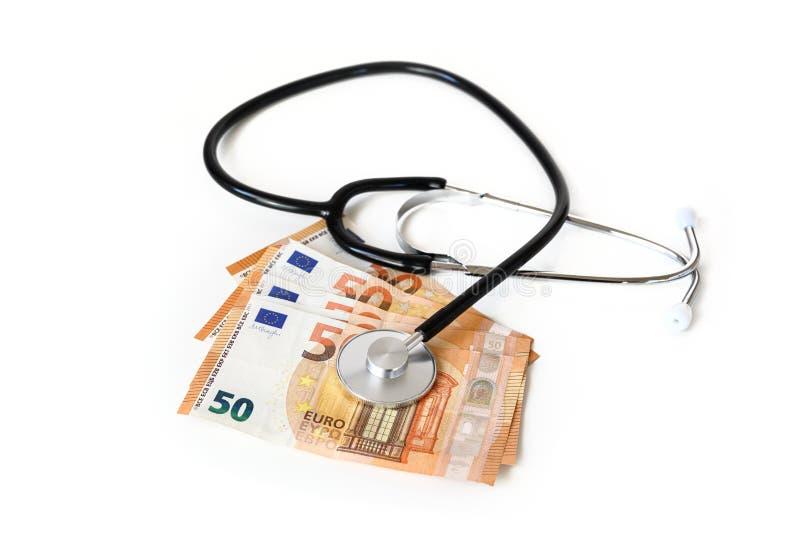 在欧元金钱钞票、医疗保健费用或者医疗腐败概念的听诊器隔绝在白色背景 免版税库存图片