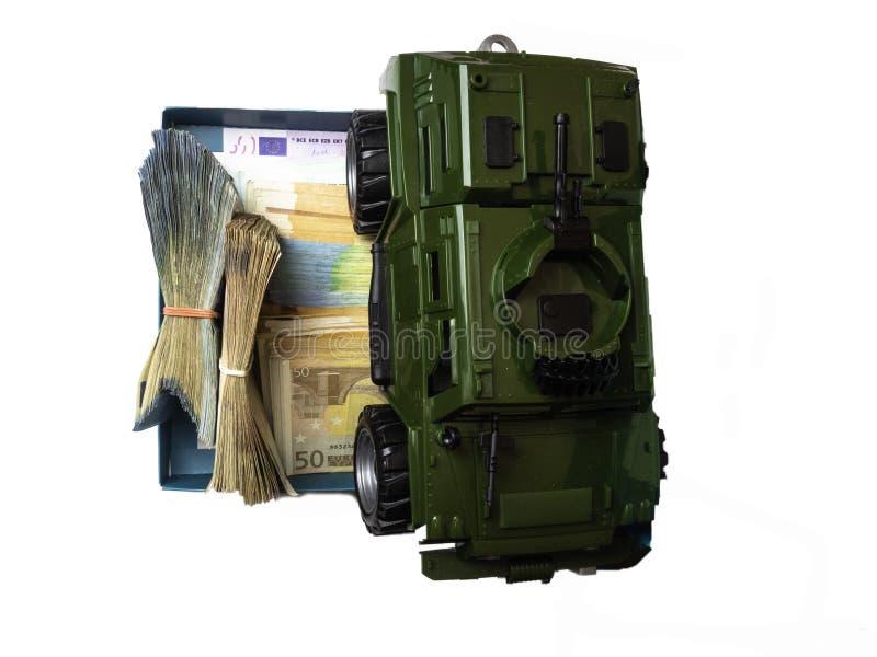 在欧元钞票堆安置的坦克玩具 事务,经济战争 从企业和经济概念的新的世界大战 费用的概念 库存图片