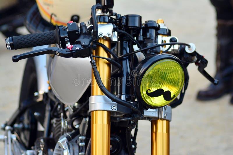在欧洲正方形的卓越的绅士的乘驾 在摩托车集会的习惯摩托车 库存图片
