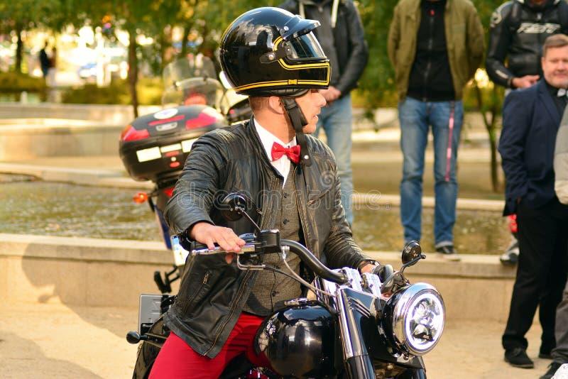 在欧洲正方形的卓越的绅士的乘驾 在摩托车集会的习惯摩托车 免版税库存照片