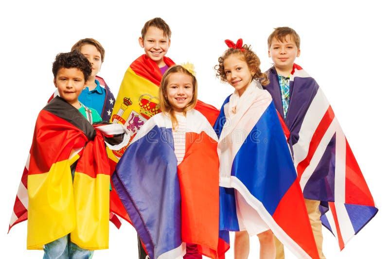 在欧洲国家旗子包裹的小组孩子 库存图片