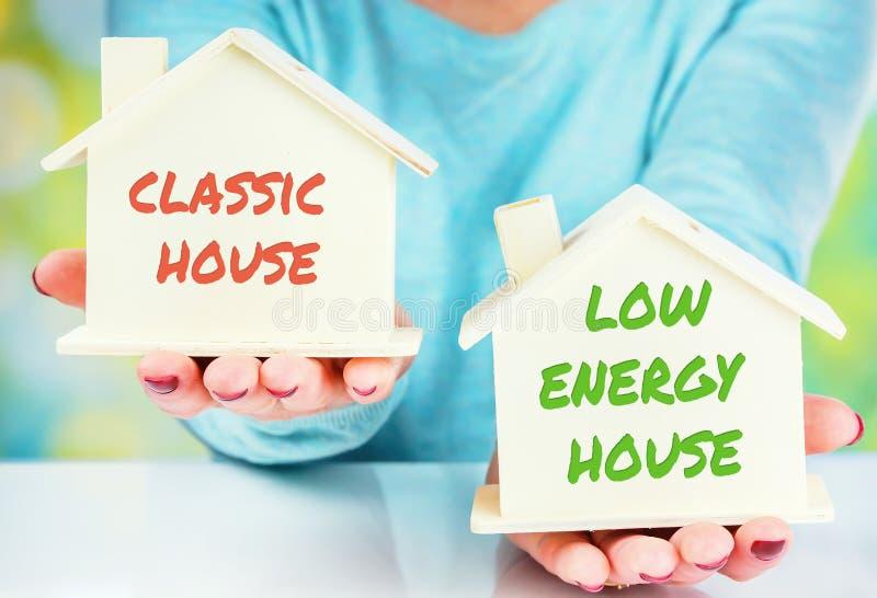 在正常房子和低消耗量房子之间的概念比较 免版税图库摄影