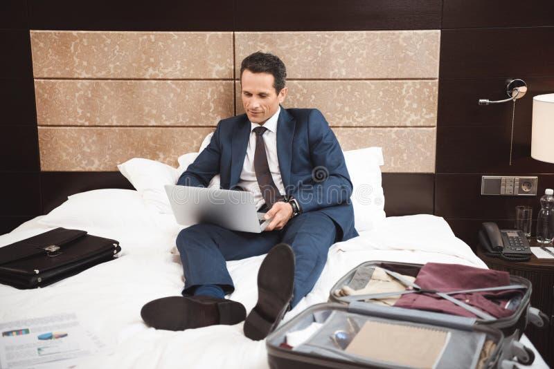 在正式衣服的年轻商人坐在旅馆客房和使用的床 免版税库存照片