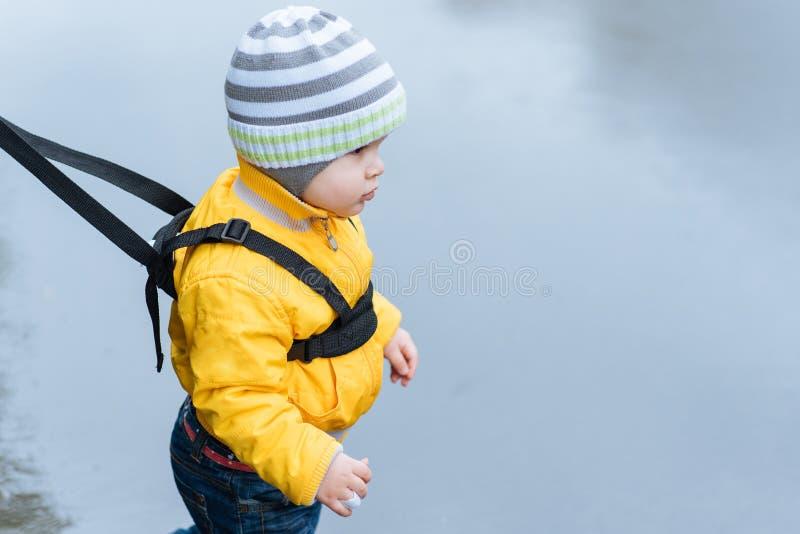 在步行期间,妈妈保险她的孩子 库存照片