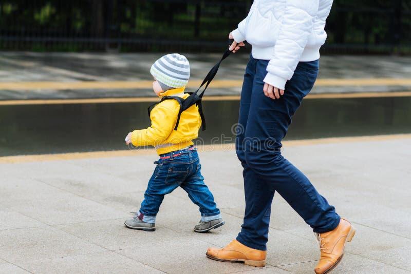 在步行期间,妈妈保险她的孩子 免版税库存图片