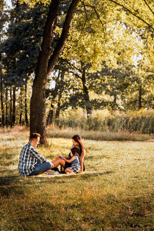 在步行的年轻家庭在森林里 免版税库存图片