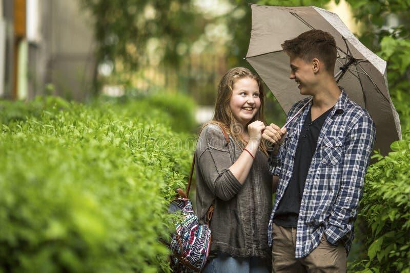 在步行的愉快的夫妇在有伞的公园 免版税库存图片