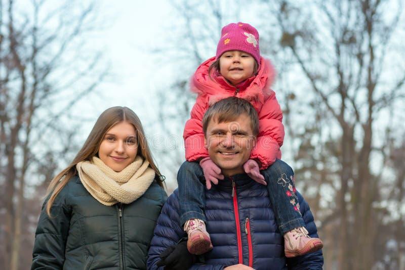 在步行的愉快的家庭在秋季森林里 库存图片