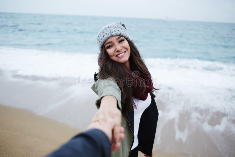 在步行的浪漫夫妇在海滩在假期时移动 免版税库存照片