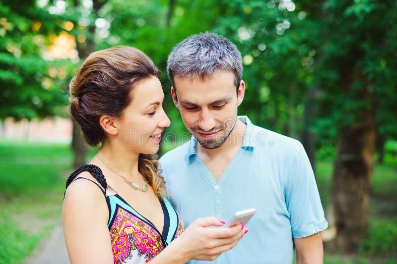 在步行的年轻夫妇与他们巧妙的电话 库存照片