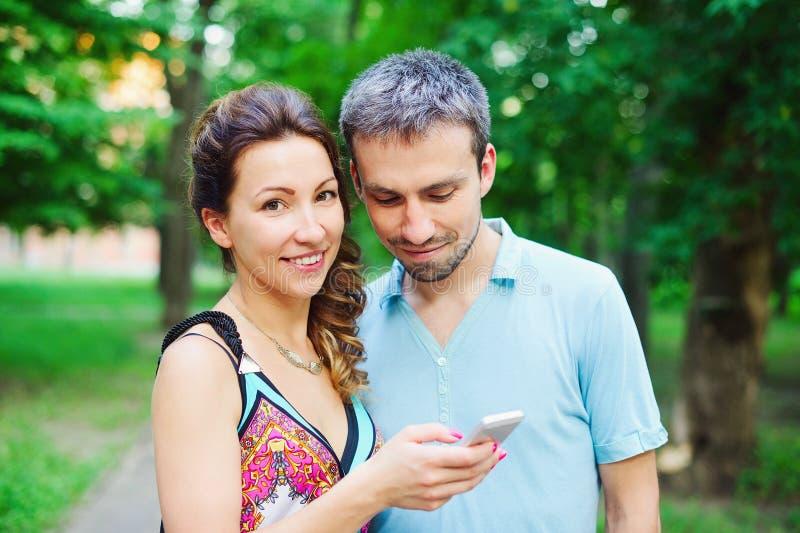 在步行的年轻夫妇与他们巧妙的电话 免版税库存照片