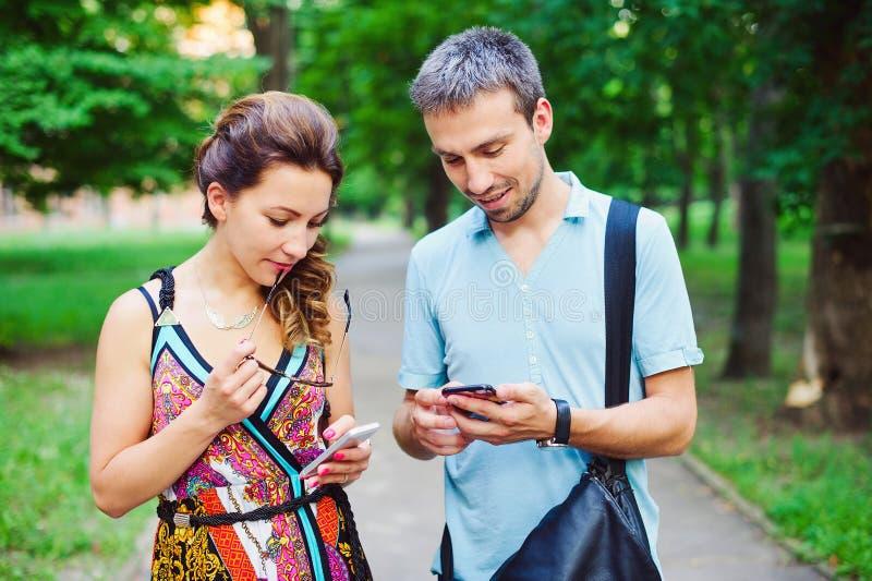 在步行的年轻夫妇与他们巧妙的电话 免版税图库摄影