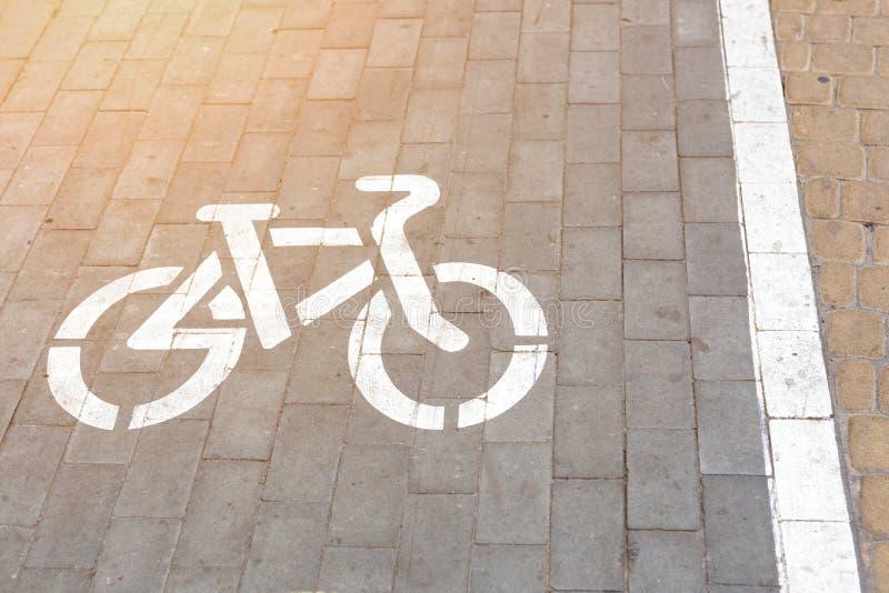 在步行走的区域的自行车平板被铺的车道 自行车标志绘与在灰色被铺的路的白色油漆 循环友好 库存照片