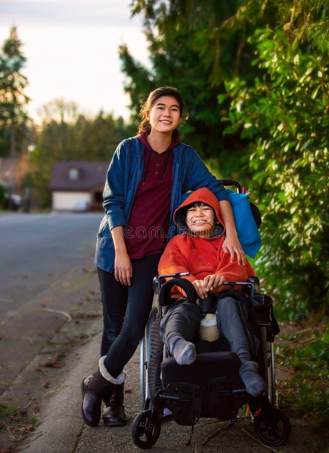在残疾弟弟旁边的姐妹身分户外轮椅的 免版税图库摄影