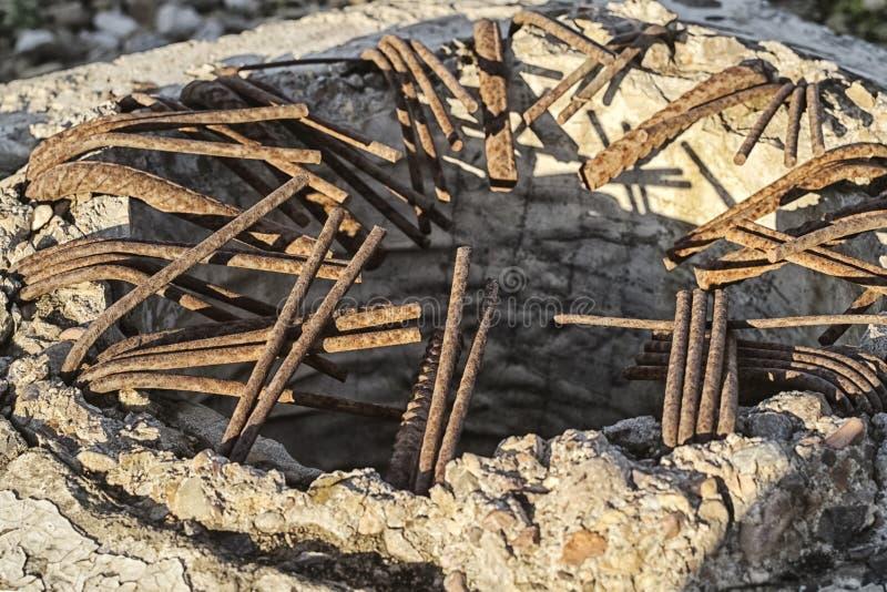 在残破的柱子的特定基地的外面弯的生锈的增强棍子 库存图片