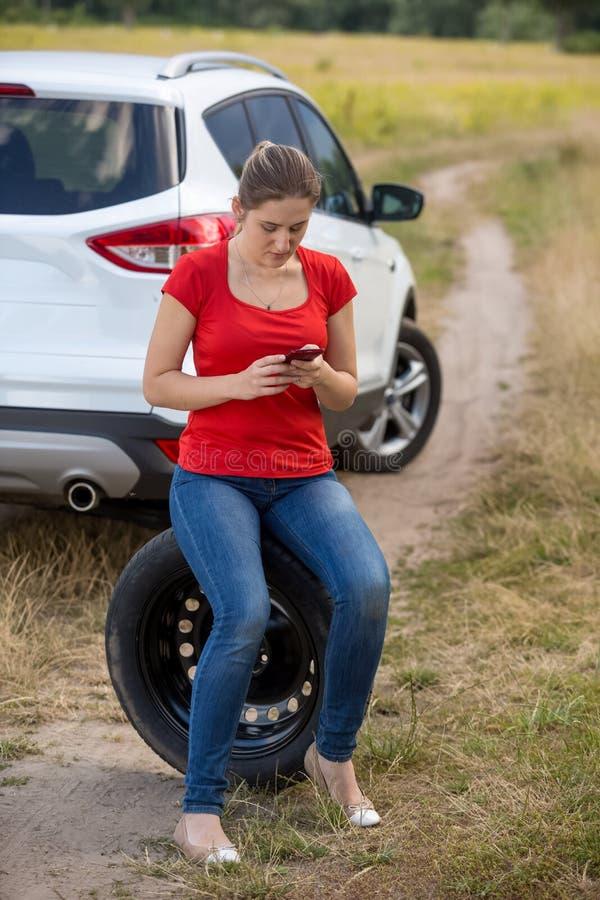 在残破的汽车旁边的少妇选址和搜寻在手机的自动服务数字 免版税库存照片