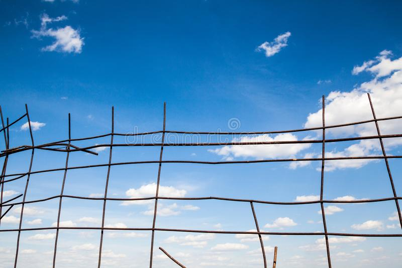 在残破的金属篱芭后的天空蔚蓝 免版税图库摄影