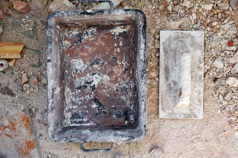 在残骸背景的泥工工具 免版税库存照片