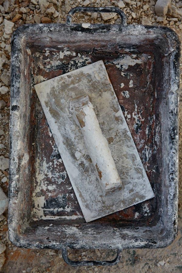 在残骸背景的泥工工具 库存图片