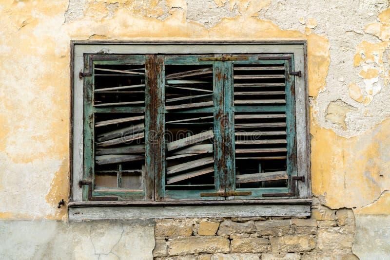 在毁坏的老残破的窗口在房子前面下的快门和奔跑与切削的油漆和膏药 库存照片