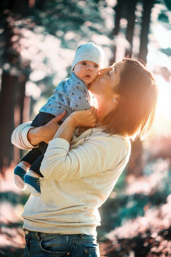 在母亲手上的男婴在公园 免版税库存图片